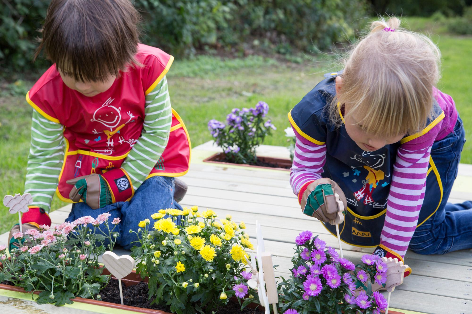 Grünes Klassenzimmer – zwei Mädchen bepflanzen einen Blumenkasten