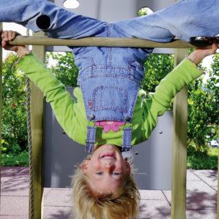 Bewegungserziehung – lachendes Kind hängt kopfüber an einer Reckstange