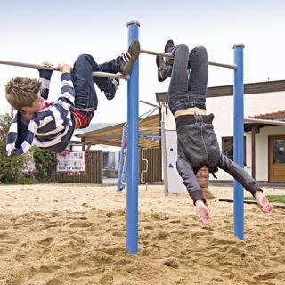 Selbstwahrnehmung bei Kindern fördern –zwei Kinder turnen nebeneinander auf zwei Reckstangen auf einem Spielplatz