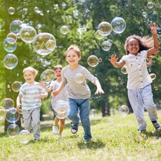 Unterschied zwischen Integration und Inklusion – vier Kinder jagen auf einer Wiese Seifenblasen hinterher