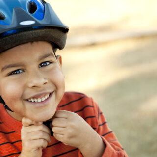 Fahrradhelm auf dem Spielplatz – Ein kleiner Junge setzt seinen Fahrradhelm auf.