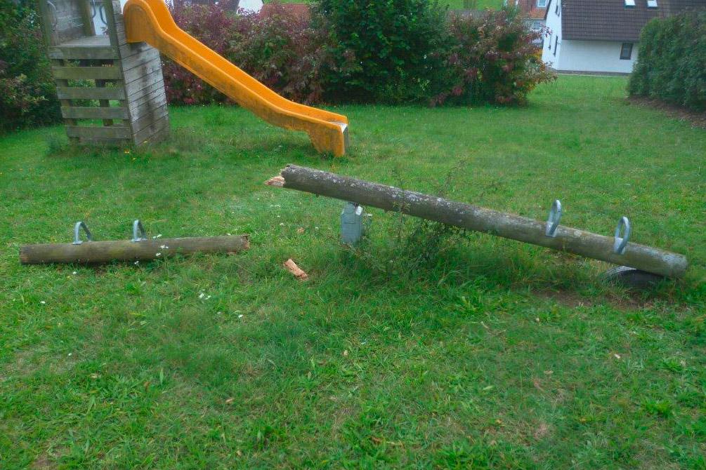 Holzspielplatz und seine Lebensdauer – Heruntergekommene Spielgeräte auf einem Spielplatz, mit einer alten, in zwei Teile gebrochenen Holzwippe im Vordergrund.