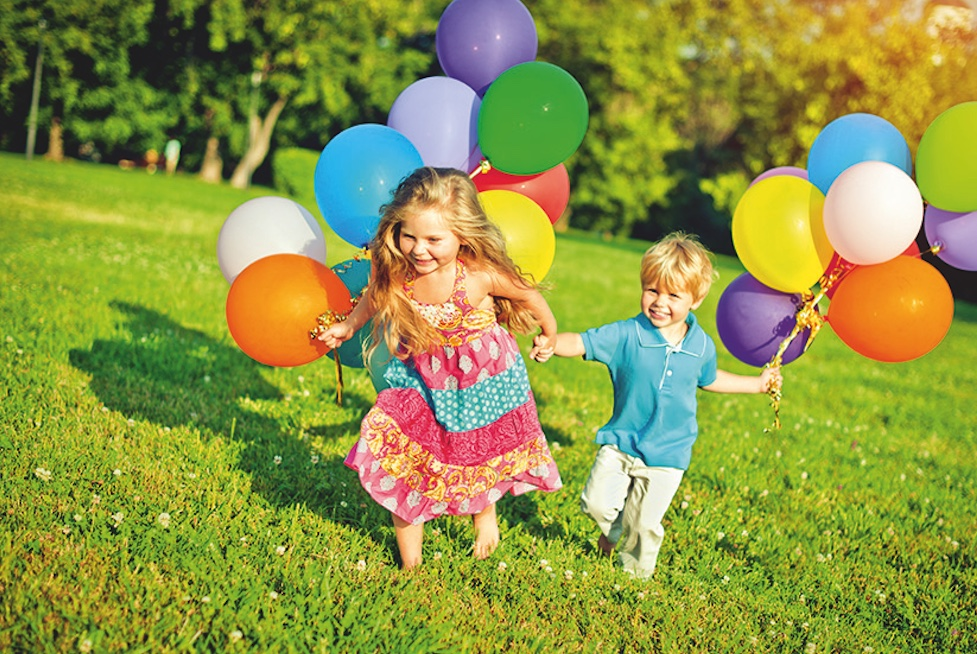 Bildung durch Bewegung - Ein Mädchen und ein Junge rennen Hand in Hand mit Luftballons über eine grüne Wiese.