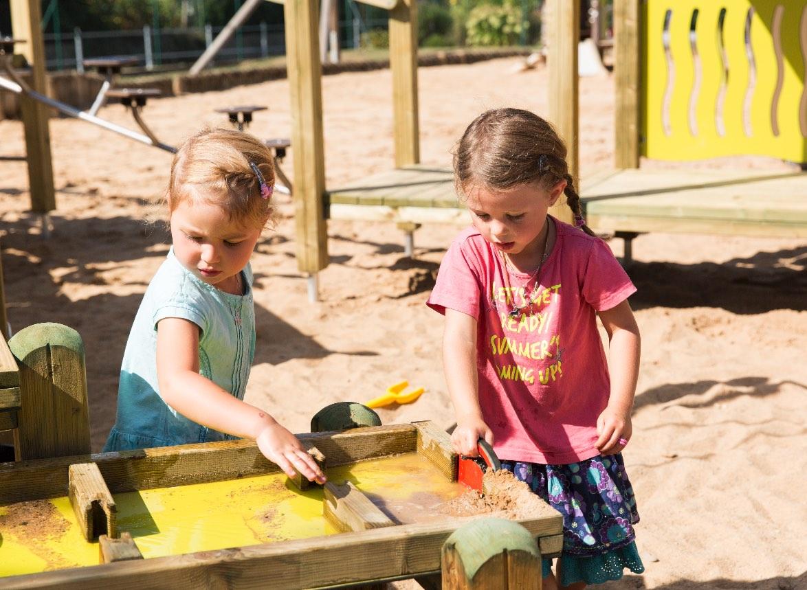 Wasserspiel & Kinder – Zwei Mädchen spielen an einer Wasserspielstation auf einem Spielplatz mit Sanduntergrund.