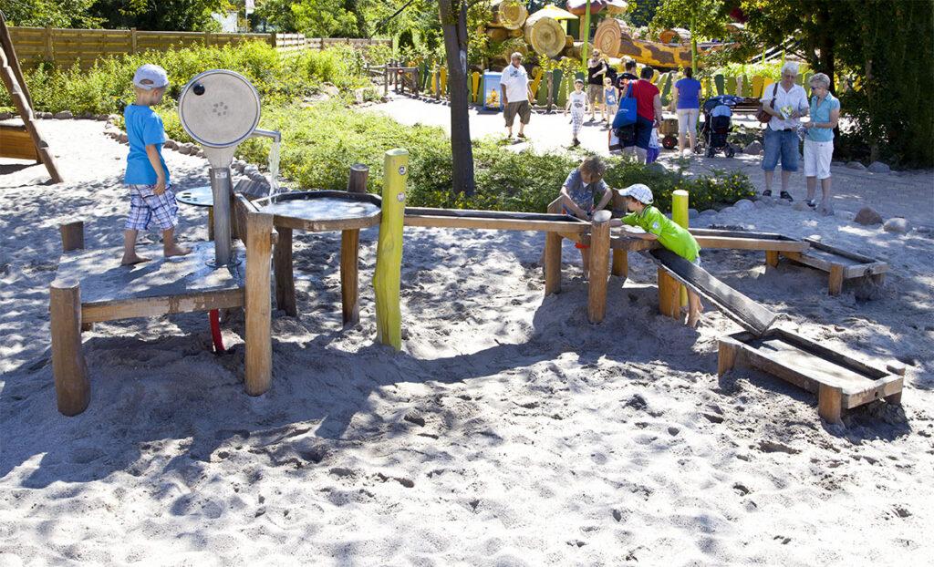 DIN 18034 - eibe Wasserspielplatz in Park mit guter Wasserqualität. Umringt von spielenden Kindern.