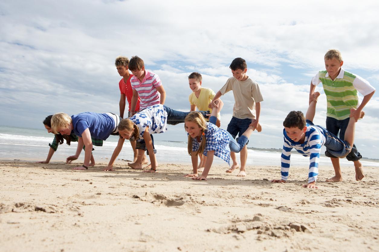 Alte Kinderspiele – Kinder spielen Schubkarrenrennen am Strand.