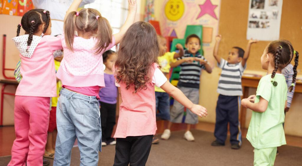 Alte Kinderspiele - Kindergartengruppe steht in einem Raum im Kreis zusammen und spielt ein Spiel.
