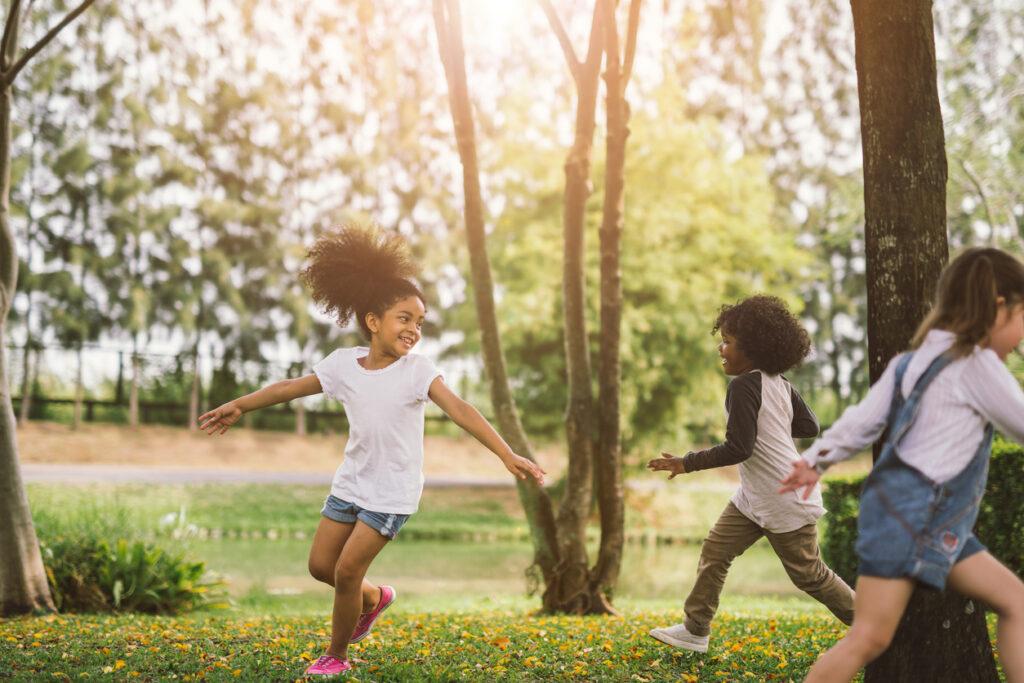Alte Kinderspiele - zwei Mädchen spielen Fangen auf einer Wiese im Park.