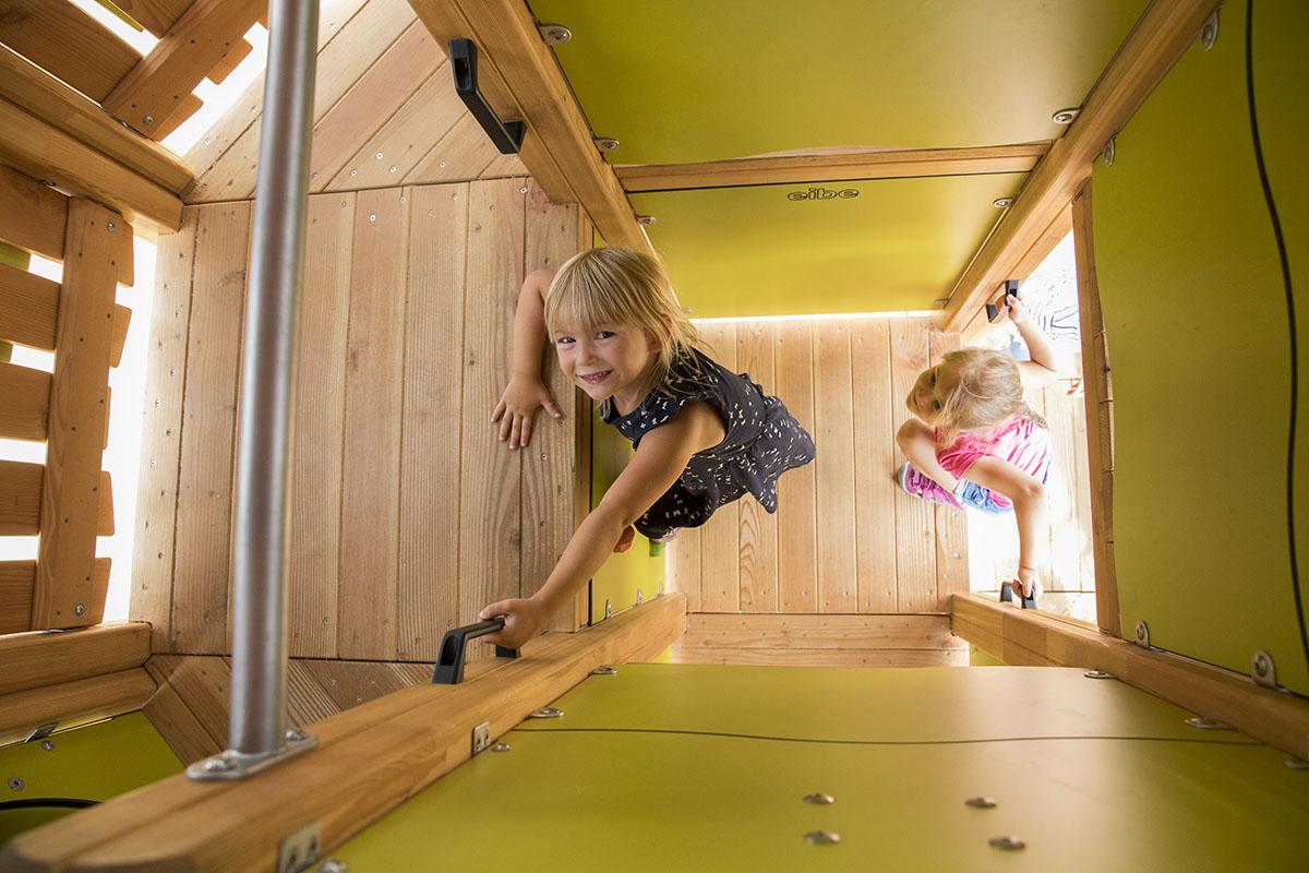 Klettern für Kinder – Zwei Mädchen klettern in das Innere eines grüngelben Spielturms.