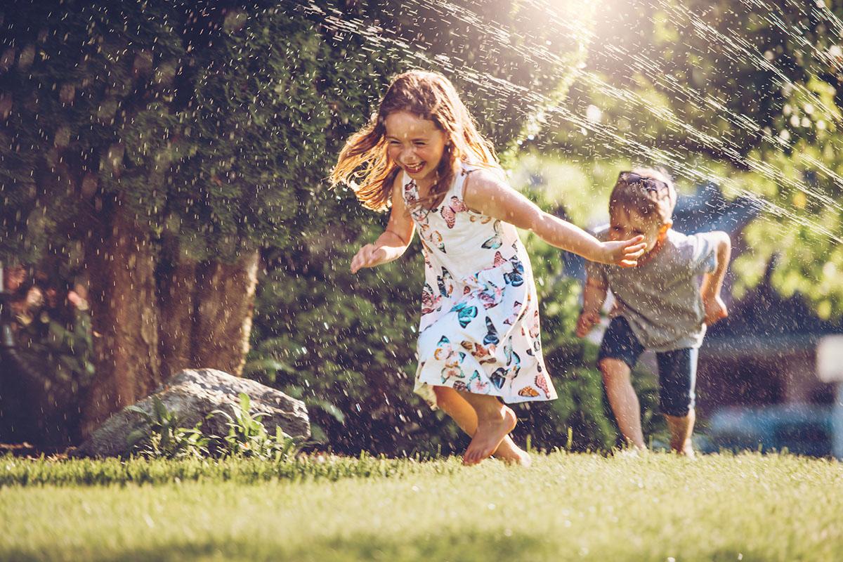 Wasserspiele für Kinder – Ein Mädchen und ein junge rennen durch die Wasserstrahlen eines Rasensprinklers.