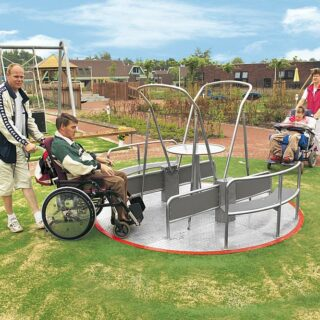 Barrierefreie Spielgeräte – Zwei Rollstuhlfahrer werden auf das Integrationskarussel geschoben.