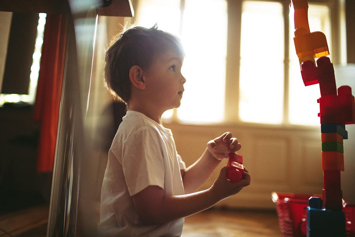 Konstruktionsspiel – ein Junge steht vor einem hohen Turm aus Duplosteinen