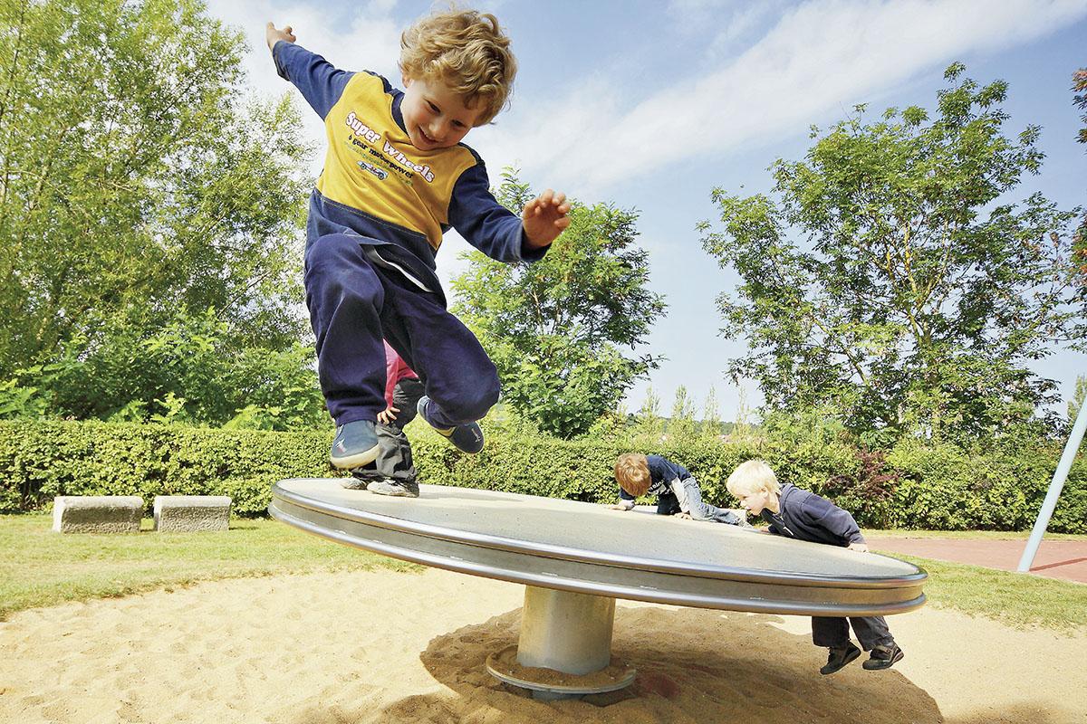 Fallschutz – ein Junge springt von einem Balancegerät auf dem Spielplatz.