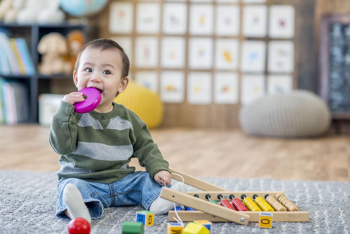 Objektspiel –ein Kleiner Junge sitzt mit seinem Spielzeug am Boden und beißt auf einen pinken Holzring.
