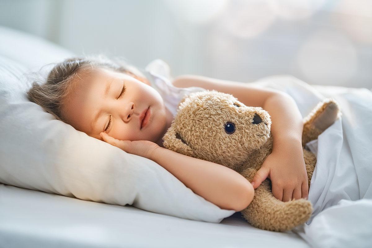 Schlafbedarf Ihrer Kinder – ein Kind schläft mit Teddy im Arm.