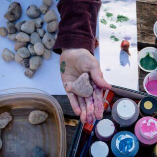 Basteln mit Naturmaterial – in einer farbbklecksten Kidnerhand liegt ein Stein.