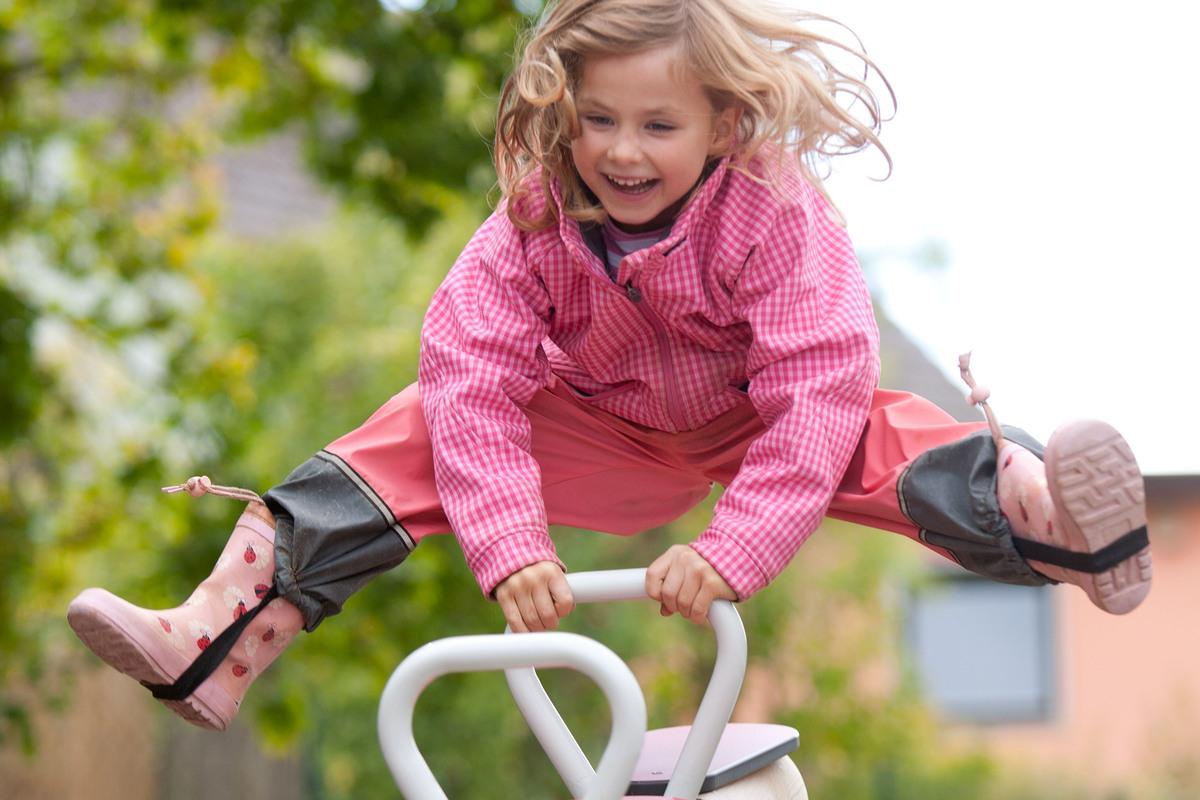 Bewegungspädagogik – Lachendes Mädchen in pinker Regenjacke und Gummistiefeln auf einer Wippe.