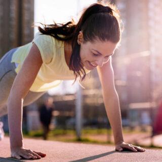 Calisthenics – eine Frau in Sportkleidung macht Liegestützen im Freien.