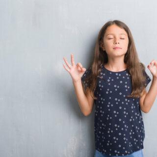 Meditation für Kinder – ein Mädchen mit geschlossenen Augen hebt die Hände zur Meditationsgeste.
