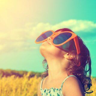 Ozonschicht – Mädchen mit übergroßer orangener Sonnenbrille schaut gen Himmel.