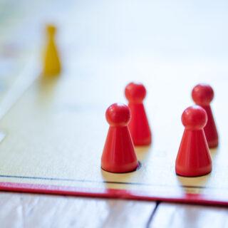 """Das Regelspiel – Teil eines """"Mensch ärgere dich nicht""""-Spielbrettes mit roten Figuren."""