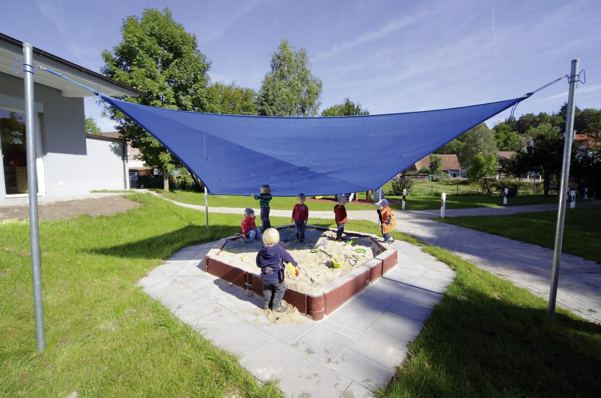 Sandkasten mit Sonnenschutz – Blaues Sonnensegel über Sandkasten mit spielenden Kindern gespannt.