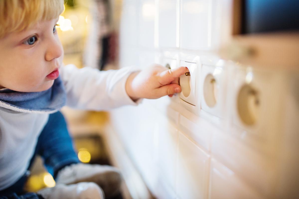 Sicherheitserziehung – ein Kind tastet mit dem Finger in einer Steckdose.