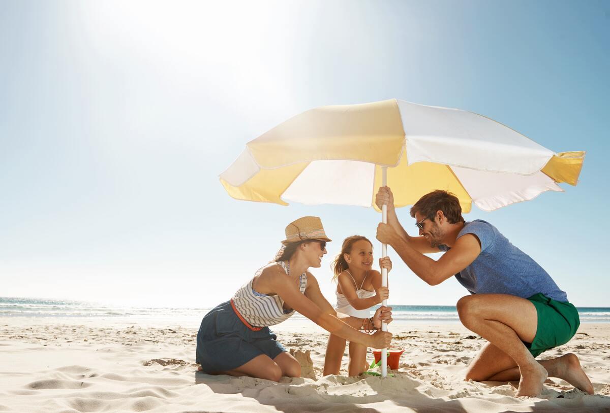 Sandkasten mit Sonnensegel – Mutter, Vater und Tochter bauen am Strand einen Sonnenschirm auf.