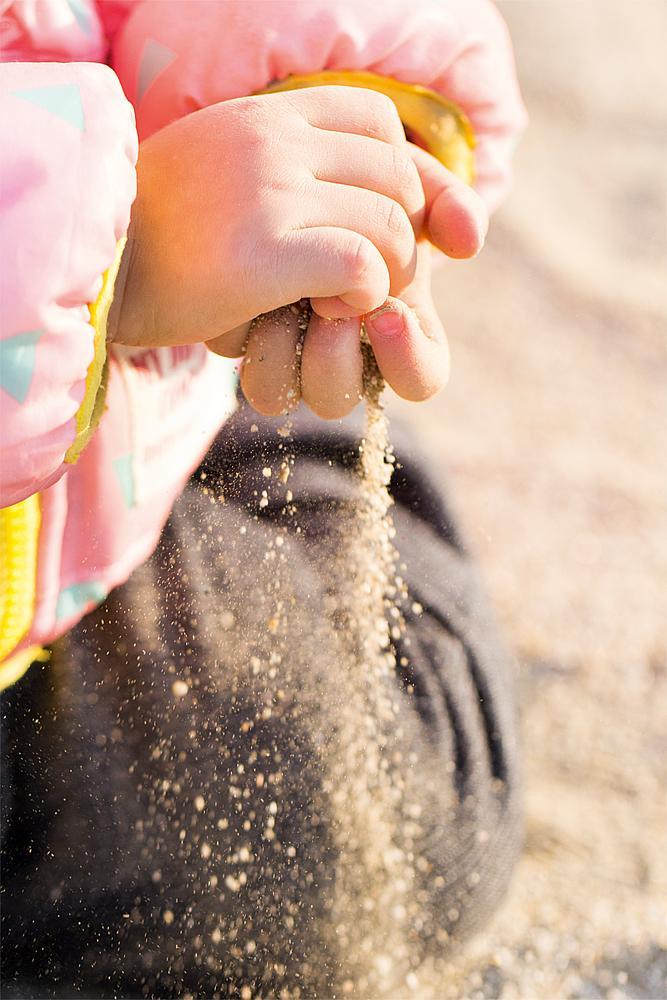 Spielen mit Sand – Kinderhände, durch die Sand rieselt