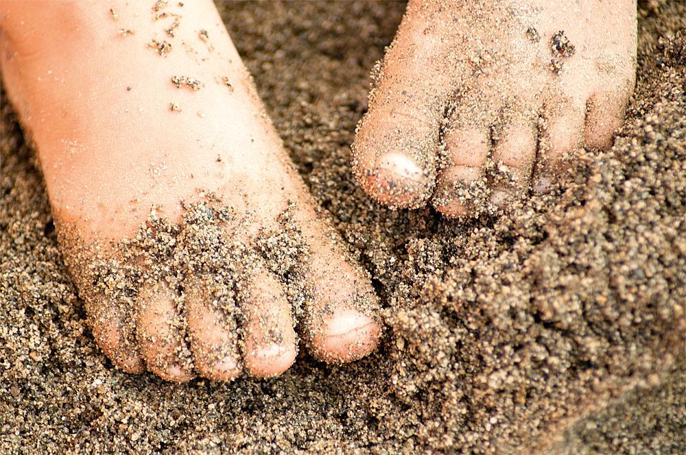 Spielen mit Sand – Kinderfüße im Sand