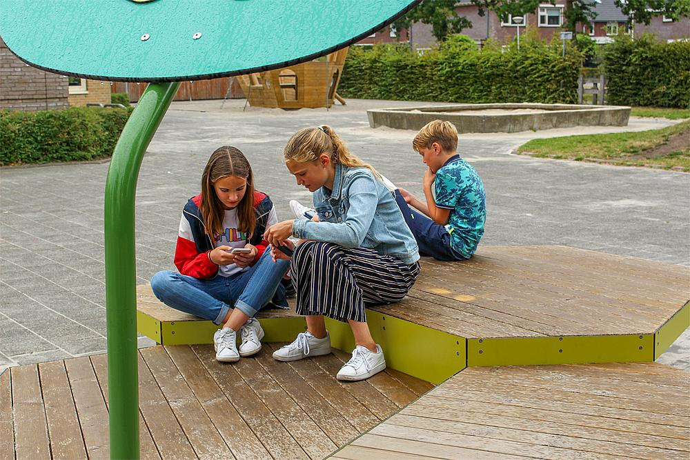 Außenmöbel für Schulen – Drei Kinder sitzen auf einem Podest auf dem Schulhof.