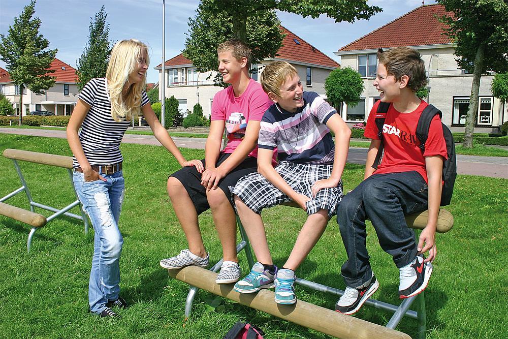 Außenmöbel für Schulen –Drei Jungs sitzen auf einem Sitzbalken von eibe, ein Mädchen steht daneben.