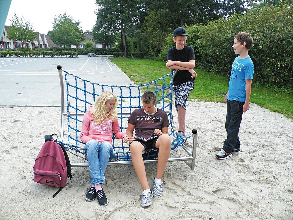 Außenmöbel für Schule – Zwei Jugendliche sitzen in einer Netzcouch, zwei weitere stehen daneben.