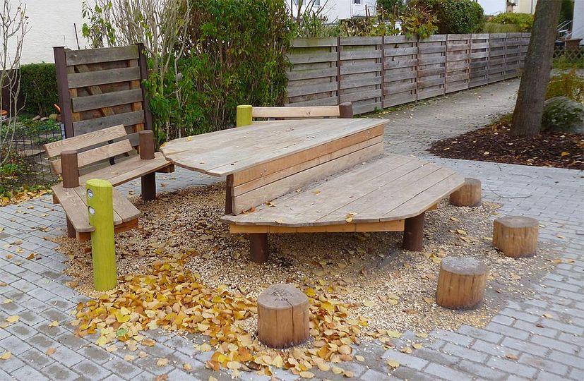 Außenmöbel für Schulen – Eine Sitzgruppe hölzerne bestehend aus Bänken, Hockern und einem Podest.