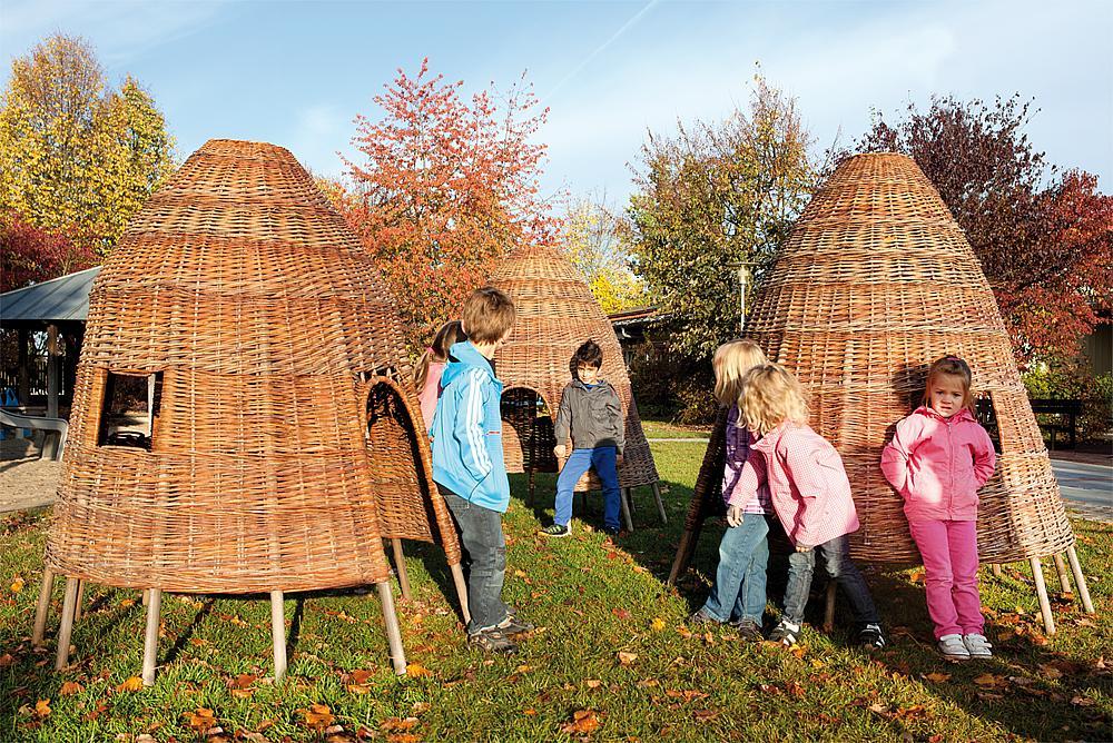 Außenmöbel für Schulen – Sechs Kinder lehnen an aus Weidenruten geflochtenen Hütten.