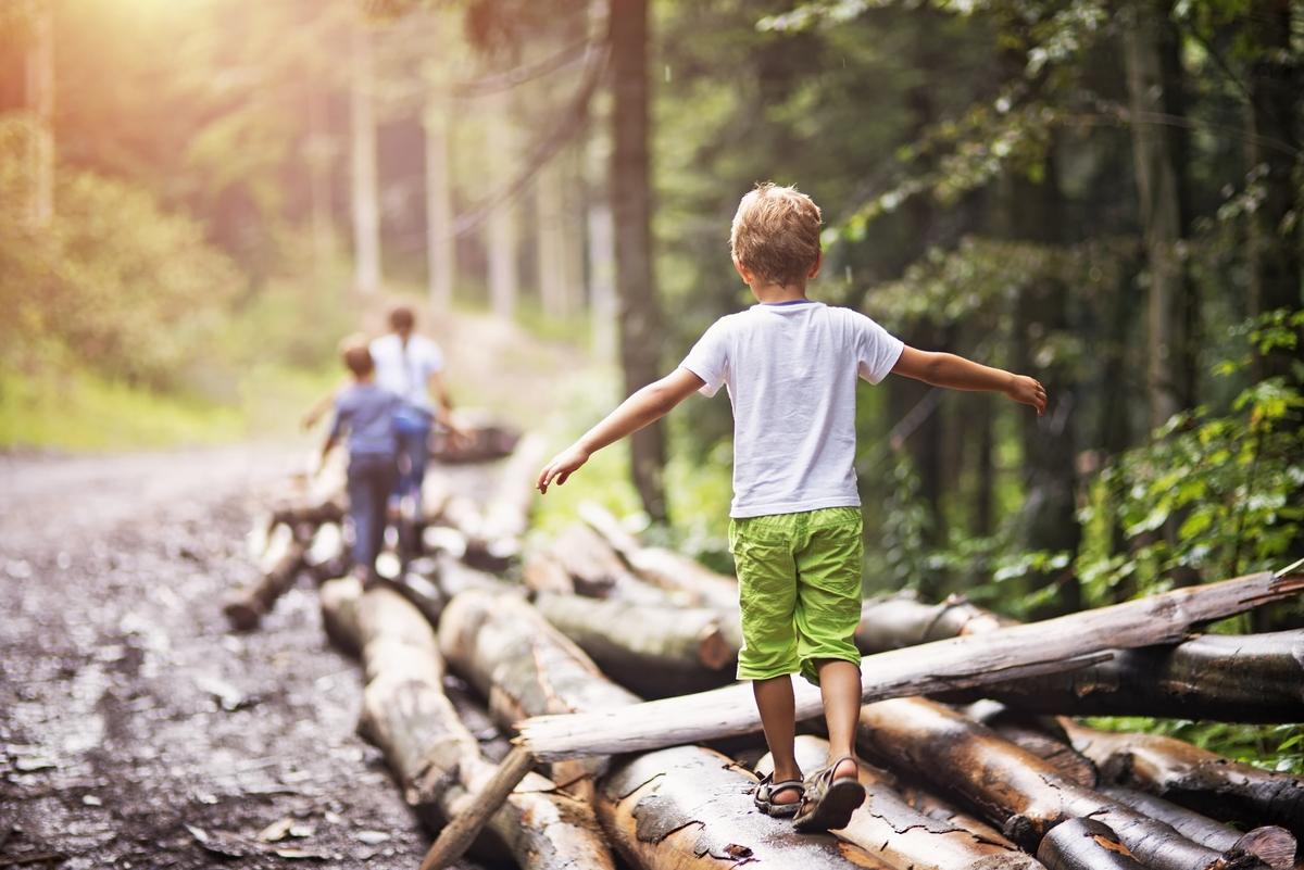 Gleichgewichtsübungen für Kinder – Jungen balancieren im Wald einige Baumstämme entlang.