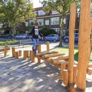 Hindernisparcours für Kinder –ein Junge balanciert über Holzpfosten
